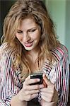 Close-up of a beautiful woman text messaging on a mobile phone Stock Photo - Premium Royalty-Free, Artist: Blend Images, Code: 6108-06166913