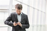 Businesswoman text messaging on a mobile phone in an office Stock Photo - Premium Royalty-Freenull, Code: 6108-06166920