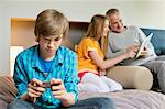 Teenage boy using mobile phone with his father and sister using digital tablet in background Stock Photo - Premium Royalty-Free, Artist: CulturaRM, Code: 6108-06166925