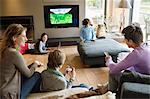Family using electronic gadgets in a living room Stock Photo - Premium Royalty-Free, Artist: Westend61, Code: 6108-06166973