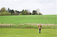 Man using a mobile phone in a field Stock Photo - Premium Royalty-Freenull, Code: 6108-06167129