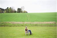 Man sitting on the bench and using a mobile phone in a field Stock Photo - Premium Royalty-Freenull, Code: 6108-06167177