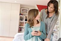Girl text messaging on mobile phone and looking at her mother Stock Photo - Premium Royalty-Freenull, Code: 6108-06167202