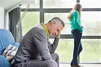 sad girls - Man looking upset with his daughter standing in the background Stock Photo - Premium Royalty-Freenull, Code: 6108-06167248