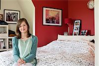 preteen beauty - Portrait of a girl sitting on the bed and smiling Stock Photo - Premium Royalty-Freenull, Code: 6108-06167309