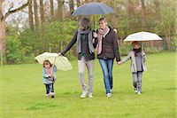 family shoes - Family walking with umbrellas in a park Stock Photo - Premium Royalty-Freenull, Code: 6108-06167317