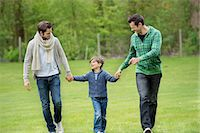 Boy walking with two men in a park Stock Photo - Premium Royalty-Freenull, Code: 6108-06167348