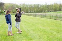 Woman with her daughter standing in a field Stock Photo - Premium Royalty-Freenull, Code: 6108-06167367