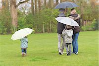 Family walking with umbrellas in a park Stock Photo - Premium Royalty-Freenull, Code: 6108-06167371
