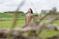 Boy daydreaming in a field Stock Photo - Premium Royalty-Freenull, Code: 6108-06167373