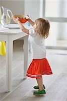 Girl setting bowl of food on a table Stock Photo - Premium Royalty-Freenull, Code: 6108-06167423