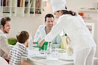 Woman serving food to her family and friends Stock Photo - Premium Royalty-Freenull, Code: 6108-06167459