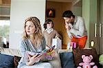 Woman sitting on couch with her husband and son holding surprise gifts in background at mother day Stock Photo - Premium Royalty-Free, Artist: Westend61, Code: 6108-06167493