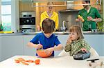Little girl with a toy car looking at his brother cooking in the kitchen Stock Photo - Premium Royalty-Freenull, Code: 6108-06167525