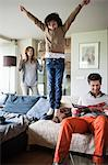 Naughty boy jumping on couch with his parents at home Stock Photo - Premium Royalty-Free, Artist: Blend Images, Code: 6108-06167531