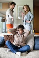 sad child sitting - Boy covering ears with hands while his parents arguing in the background Stock Photo - Premium Royalty-Freenull, Code: 6108-06167546