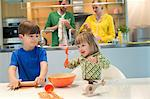 Children cooking in the kitchen with their parents in the background Stock Photo - Premium Royalty-Free, Artist: Cultura RM, Code: 6108-06167573