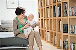 Woman sitting on a couch playing with her granddaughter Stock Photo - Premium Royalty-Free, Artist: Blend Images, Code: 6108-06167639