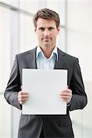 person holding sign - Businessman holding a blank placard in an office Stock Photo - Premium Royalty-Freenull, Code: 6108-06167880