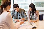Couple signing documents with business executive Stock Photo - Premium Royalty-Free, Artist: Blend Images, Code: 6108-06167913