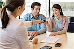 Couple receiving keys from business executive Stock Photo - Premium Royalty-Free, Artist: Blend Images, Code: 6108-06167915