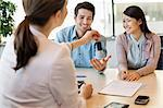 Couple receiving keys from business executive Stock Photo - Premium Royalty-Free, Artist: Blend Images, Code: 6108-06167939