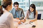 Couple signing documents with business executive Stock Photo - Premium Royalty-Free, Artist: Blend Images, Code: 6108-06167963