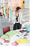 Female fashion designer talking on a mobile phone in an office Stock Photo - Premium Royalty-Free, Artist: Blend Images, Code: 6108-06168221