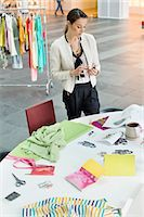 Female fashion designer text messaging in an office Stock Photo - Premium Royalty-Freenull, Code: 6108-06168267