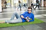 Businessman listening to music and reading book while relaxing on grass mat in an office lobby Stock Photo - Premium Royalty-Free, Artist: Cultura RM, Code: 6108-06168275