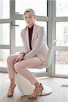 Businesswoman sitting on a chair Stock Photo - Premium Royalty-Freenull, Code: 6108-06168377