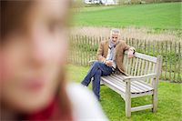 farm phone - Close-up of a girl with her father text messaging in the background Stock Photo - Premium Royalty-Freenull, Code: 6108-06168482