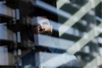 Businessman looking through window Stock Photo - Premium Royalty-Freenull, Code: 614-06168676