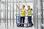Two men in empty warehouse with trolley Stock Photo - Premium Royalty-Free, Artist: AWL Images, Code: 614-06168824
