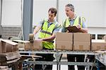 Men packing cardboard box in warehouse Stock Photo - Premium Royalty-Free, Artist: Cultura RM, Code: 614-06168857