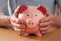 savings - Senior woman holding piggy bank Stock Photo - Premium Royalty-Freenull, Code: 614-06169301