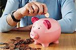 Senior woman inserting coins into piggybank Stock Photo - Premium Royalty-Free, Artist: Aurora Photos, Code: 614-06169316