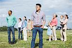 Young man standing in front of group of people outdoors Stock Photo - Premium Royalty-Freenull, Code: 614-06169590