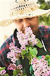 Spring garden concept. Male gardener is doing garden work around lilac flowers. Stock Photo - Royalty-Free, Artist: mythja                        , Code: 400-06170631