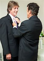 One groom straightens the other groom's tie at a gay marriage reception. Stock Photo - Royalty-Freenull, Code: 400-06172883