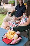 Couple sitting on terrace, chips in foreground Stock Photo - Premium Royalty-Freenull, Code: 659-06184438