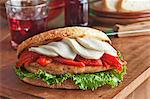 Grilled Chicken Breast Sandwich with Roasted Red Peppers, Mozzarella Cheese and Lettuce on Grilled Tuscan Boule Bread Stock Photo - Premium Royalty-Freenull, Code: 659-06188425
