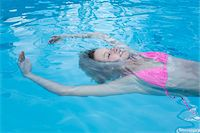 Teenage Girl Floating in Swimming Pool Stock Photo - Premium Rights-Managednull, Code: 700-06190525