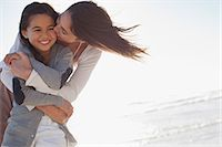 daughter kissing mother - Mother hugging and kissing daughter on beach Stock Photo - Premium Royalty-Freenull, Code: 635-06191625