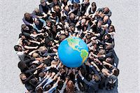 Crowd of business people in huddle reaching for globe Stock Photo - Premium Royalty-Freenull, Code: 635-06191676