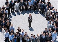 Portrait of businesswoman standing at center of circle formed by business people Stock Photo - Premium Royalty-Freenull, Code: 635-06191679
