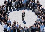 Portrait of businesswoman standing at center of circle formed by business people Stock Photo - Premium Royalty-Free, Artist: Blend Images, Code: 635-06191679