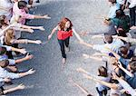 Woman walking through crowd with arms outstretched Stock Photo - Premium Royalty-Free, Artist: Blend Images, Code: 635-06191694