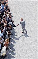 Businessman shaking man's hand in crowd Stock Photo - Premium Royalty-Freenull, Code: 635-06191709
