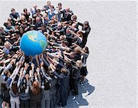 Crowd of business people in huddle reaching for globe Stock Photo - Premium Royalt